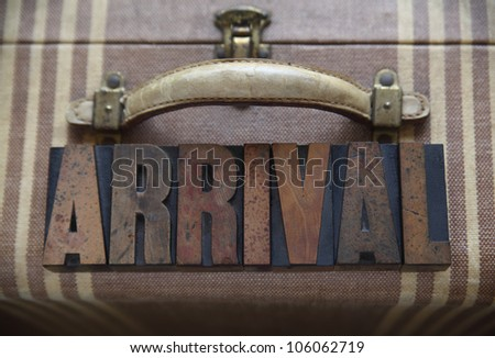 he word arrival in old wood type on a well-used suitcase