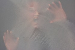 Head and handprint of woman as she suffocates behind fabric, raised hands and wide open mouth. Mystery concept. Shadow blur of screaming woman. Touching the void. Close up photo.