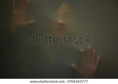 Head and handprint of woman as she suffocates behind fabric, raised hands and wide open mouth. Mystery concept. Shadow blur of screaming woman. Touching the void. Close up photo.   Stockfoto ©