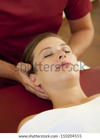 head and neck massage of a beautiful woman. a woman receives a pressure point reflexology massage by her chiropractor.