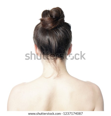 head and shoulder back view of young woman with messy bun - undone hair style fashion trend
