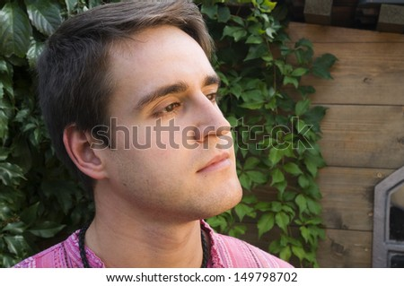 Head and shoulder portrait of a young man facing to the side out of a log cabin