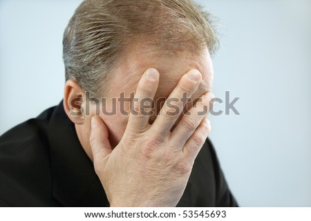 Head and shoulder portrait of middle aged  Caucasian businessman covering face with hand.