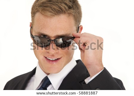 Head and shoulder portrait of young businessman wearing a suit and sunglasses