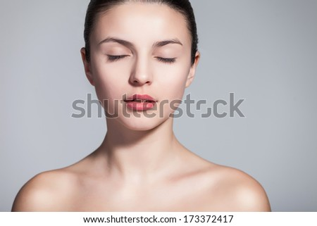 Head and shoulder shot of a beautiful young woman in the nude with eyes closed over gray background