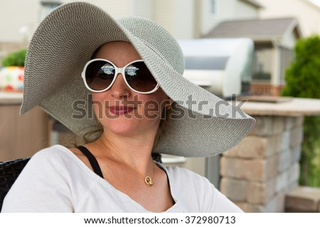 Head and Shoulders Close Up of Joyful Woman Wearing Large Brimmed Sun Hat and Sunglasses Smiling and Looking to the Side Outdoors on Backyard Patio on Sunny Day #372980713
