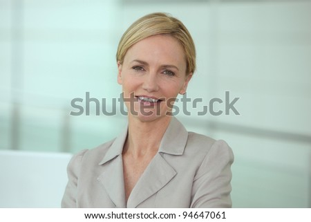 Head and shoulders of a smiling businesswoman in a biege suit