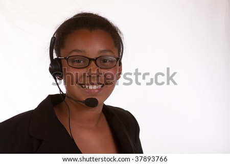 Head and shoulders of a young African American business woman wearing headset over white
