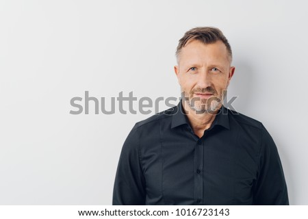 Head and shoulders portrait of a bearded middle-aged man looking thoughtfully at the camera over a white studio background with copy space