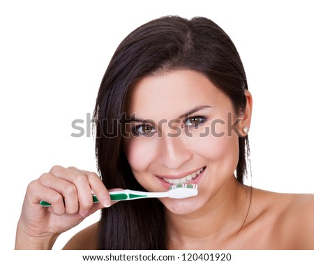 Head and shoulders portrait of a beautiful woman brushing her teeth and smiling at the camera isolated on white