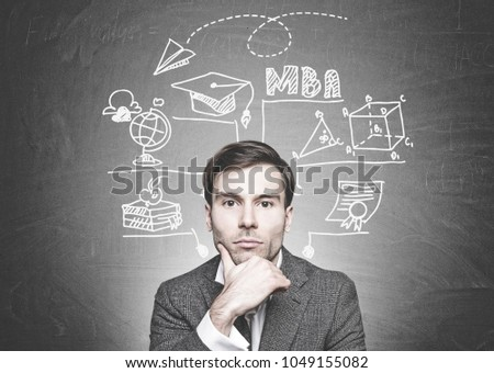 Head and shoulders portrait of a thoughtful young businessman with dark hair looking at the camera. A blackboard with a business education sketch. MBA
