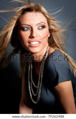 Head and shoulders portrait of a young blond lady with beautiful blond hair, posing over gray background. Studio shot. Artistic colors added.