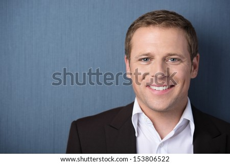 Head and shoulders portrait of a young friendly smiling business man looking at the camera against a blue background with copyspace