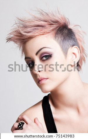 Head and shoulders portrait of an attractive young woman with wild pink hair. Vertical shot. - stock photo