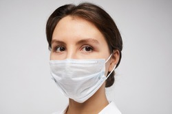 Head and shoulders portrait of female doctor wearing protective mask and looking at camera posing against white background