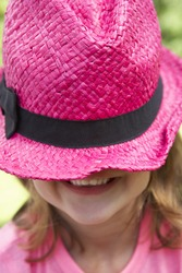 Head And Shoulders Portrait Of Girl Wearing Pink Straw Hat