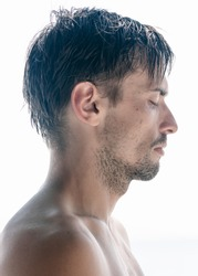 Head and shoulders profile portrait of a tousled unshaven shirtless young man with closed eyes and a serious expression isolated on white