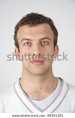 Head and shoulders shot of a young caucasian man looking straight at the camera with a neutral look