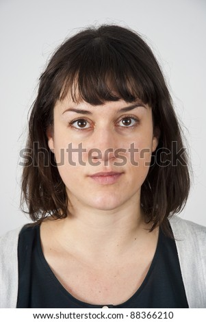 Head and shoulders shot of a young caucasian woman looking straight at the camera with a very neutral look