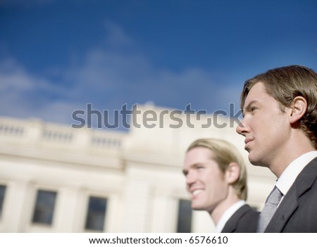head and shoulders view of two business men well dressed standing side by side next to courthouse looking away