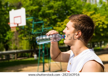 Head and Shoulders View of Young Man Drinking Water from Bottle, Taking a Break for Refreshment and Hydration on Basketball Court