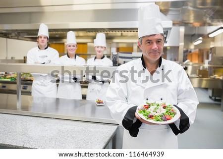 Head chef presenting salad with his team standing behind him