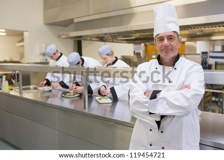 Head chef smiling in busy kitchen with team working behind him
