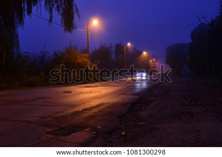 Stock Photo Head lights of the car moving on the damaged asphalt road lit by electric poles on the early misty autumn morning
