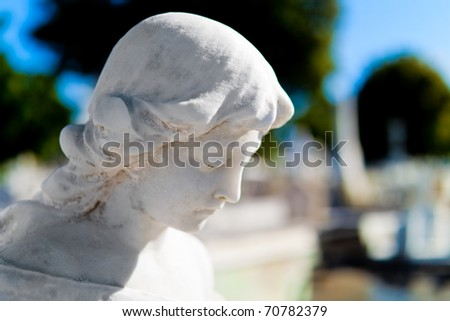 Head of a beautiful marble angel with a diffused graveyard background