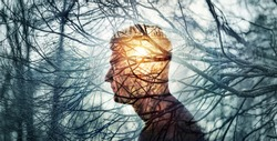 Head of a man on background of trees in forest. Concept on topic of psychology, psychiatry, depression. The branches of trees symbol problems and diseases and sun is a symbol of hope and recovery.
