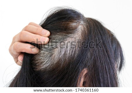 Head of an elderly woman with gray hair that grew after dyeing ストックフォト ©