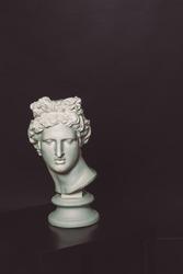 Head of Apollo. Greek statue. Greek god Apollo. Head of Apollo. Greek statue on the table. Black background.