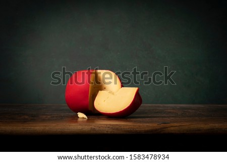head of Edam cheese with a red crust lying on a brouwn wooden table with a green background. Rembrandt lightning style