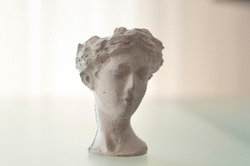 Head of female Greek statue. Greek statue on the table. White statue on glass desk. Marble head in the living room, curtains in the background. Sunlight on the background.