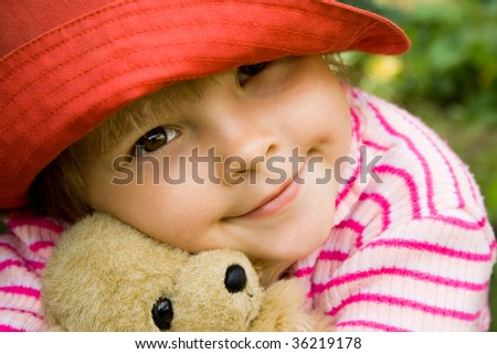 Head of girlie embracing her teddy-bear with peaceful expression