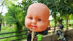 Head of little doll and straw in a hand. indian toys and doll market. beautiful doll face, head with blured background.