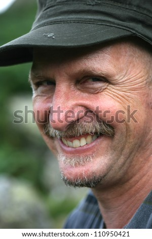 Head of man in green base ball cap