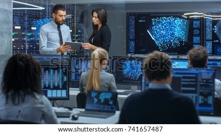 Head of the Department and Project Manager Discuss Work Process Using Data on Tablet Computer. Multi-Ethnic Team Builds Neural Network with Integrated Machine Learning.