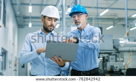 Head of the Project Holds Laptop and  Discusses Product Details with Chief Engineer while They Walk Through Modern Factory. #782842942