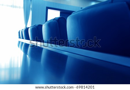 Head office boardroom with leather chairs, blue tone.