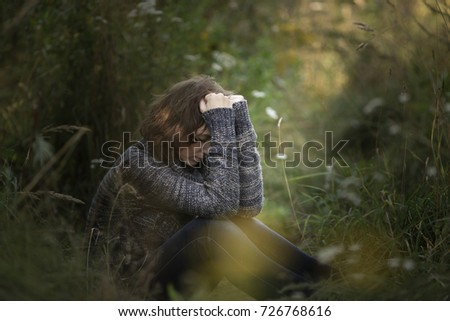 head on hands, beautiful brunette woman yearns and sadness outdoors, concept depressed and lonely, dark style in nature #726768616