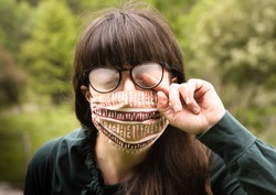 Head Portrait of Adult Brunette Woman  Wearing Dotted Protective Mask Outdoors, Cleaning Annoying Fog from Glasses