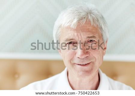 Head portrait of serene grey-haired senior man looking at camera