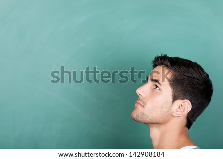 Head profile portrait of a thoughtful young male student in front of a green blackboard looking up towards copyspace on the board