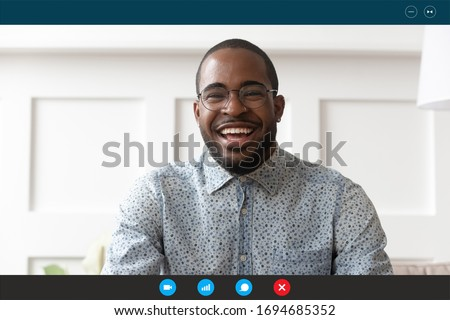 Head shot African guy sit on sofa look at webcam laptop screen view. Online edating service user, teacher provide class distantly by videocall, informal communication via videoconferencing app concept