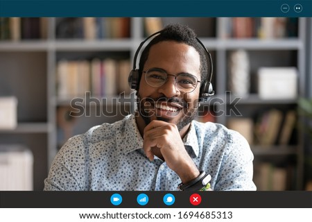 Head shot African man wear headset sit at desk look at cam use videocall conferencing app, pc screen view. Company consultant, teacher portrait, easy e-learn, distant communication with client concept