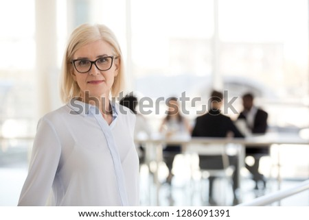 Head shot aged company owner confident woman standing apart of employees looking at camera. Experienced worker, business coach posing in modern office. Leadership and successful business lady concept