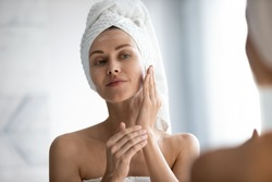 Head shot close up beautiful peaceful woman applying moisturizer on skin, looking in mirror, standing in bathroom, pretty young female with white bath towel on head using cream, touching face