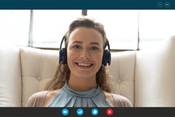 head shot close up computer screen view beautiful young smiling woman in headphones sitting on chair, holding online video call, happy female freelance worker communicating remotely with clients.