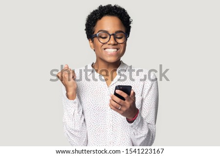 Head shot close up happy African American girl in glasses using phone, celebrating success, online win, excited young woman reading good news, showing yes gesture, isolated on grey background
